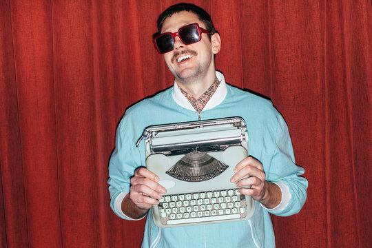 Funny smiling handsome man posing in blue jacket holding vintage typewriter in hands