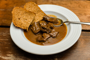 Beef stew with bread on a white plate and spoon.