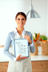 Woman in the kitchen at home, standing near desk with folder