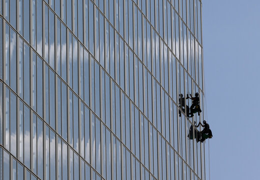 Workers make their way up a high-rise building to clean windows in Vienna