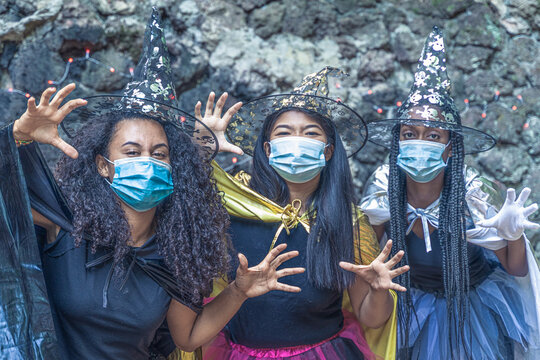 Three happy young women in witch halloween costumes on coronavirus year. Girls are playing trick or treat in halloween costumes. Halloween and virus concept.