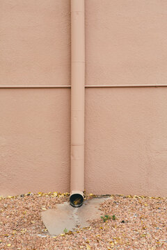 Adobe colored gutter pipe and autumn leaves