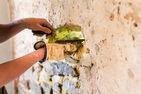 young man fixing a stone wall, home renovation