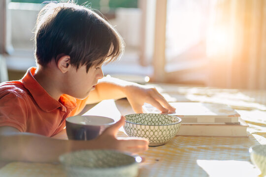 Thoughtful child boy wearing an orange t-shirt with down syndrome sitting at table and reading book at home.
