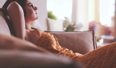 Relaxed woman sitting on a modern sofa at home