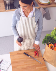 Woman with shopping bags in the kitchen at home, standing near desk