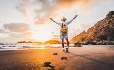 Happy traveller hiker with arms up enjoying freedom and sunset at the beach. Success, personal care, travel concept.