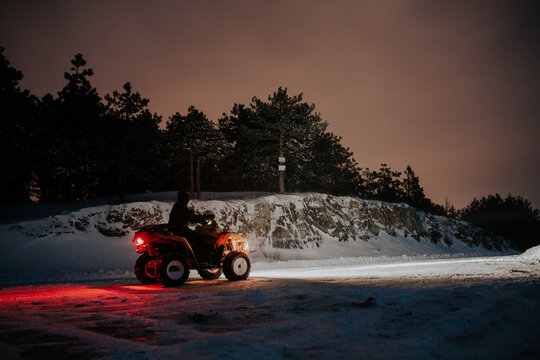 Man driving ATV on a road covered with snow