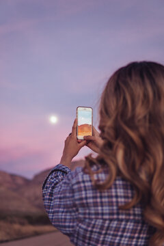 Woman taking a picture of the moon at sunset with her phone