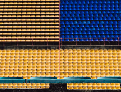 Empty out of focus blue and yellow seats on the stadium