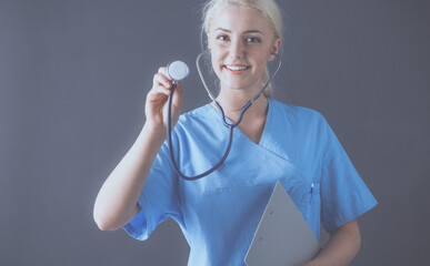 Female doctor with a stethoscope listening, isolated on gray background