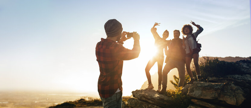 Man photographing his friends on mountain top