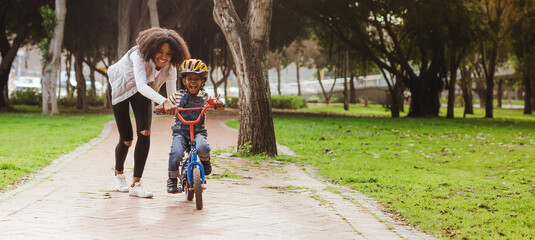 Fototapeta Little boy learning to ride bicycle at park with mother obraz