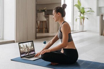 Yoga teacher conducting virtual yoga class at home on a video conference. Beautiful fit woman practicing online yoga in her living room with laptop. Home fitness and workout concept. Online training