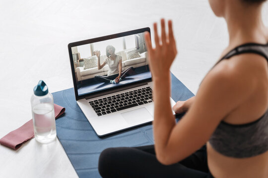 Close up of young fit woman coach in sportswear conducting online fitness training or virtual yoga class on a video conference with laptop. Home workout training. Health practice and wellness concept
