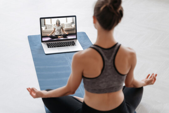 Close up of young sporty woman practicing yoga online with laptop at home. Yoga instructor conducting video training via video conference. Meditation, Sukhasana, relax. Healthy lifestyle concept