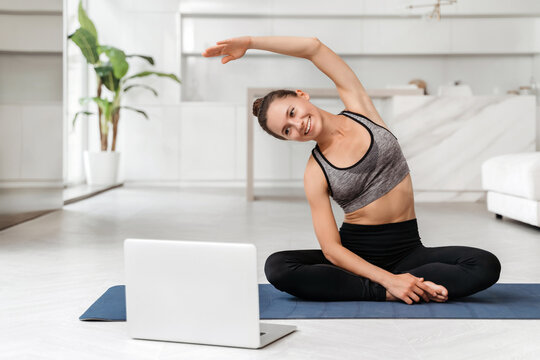 Young fit woman in sportswear practicing yoga at home with online training on laptop, watching virtual classes and tutorials. Quarantine sport, fitness and workout. Coach conducts virtual yoga lesson