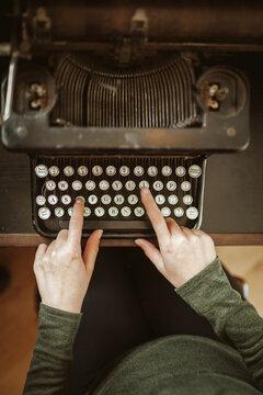 Woman typing on an old typewriter.