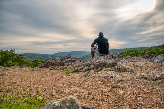 African American man sitting at the the top of a mountain enjoying the view during a hike.