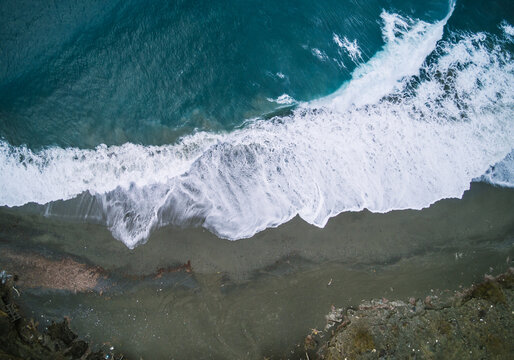 drone shot of waves breaking on the beach from above, greece, cr