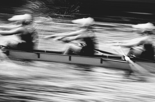 Competitive crew racers rowing scull boat, blurred motion