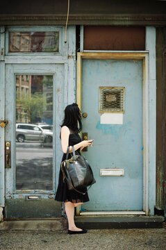 Woman in Little Black Dress with Cellphone Waiting outside a Residential Door