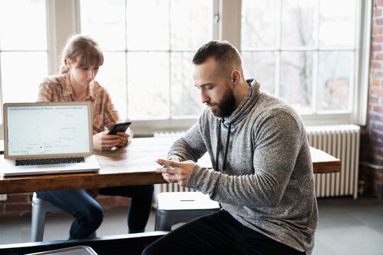 Man and woman at office table look down at their own cell phones