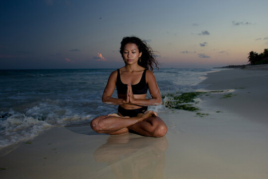 Young woman practice yoga meditation at the beach