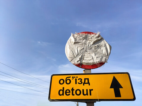 Detour road sign with the same inscriptions in English and Ukrainian, another sign above, wrapped in burlap, electric wires and blue sky in the background