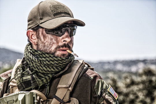 Shoulder portrait of commando fighter, professional mercenary or special forces shooter with dirty face, wearing shemagh scarf, ballistic glasses and cap, carrying service rifle and smoking cigarette
