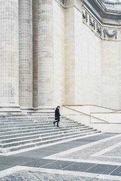 Woman walking against minimal architecture