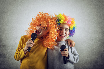 Two child sing a song with microphone and funny wig