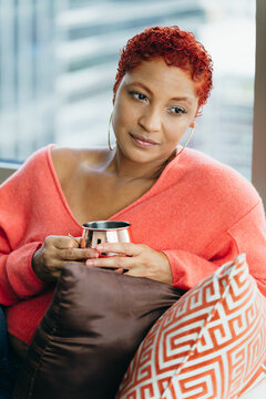 Black woman relaxing and drinking tea at home on couch