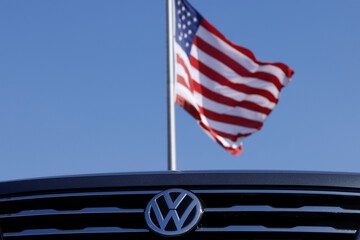 Volkswagen logo and American flag are shown at car dealershio in California