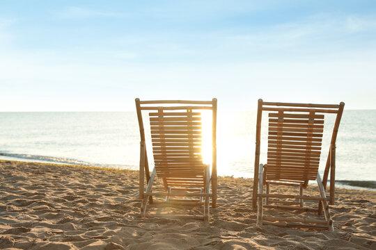 Wooden deck chairs on sandy beach. Summer vacation