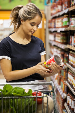 Woman reads nutrition label while grocery shopping.