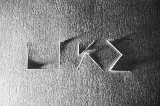 Like word cropped on cardboard. Social media icon. Black and white photo.