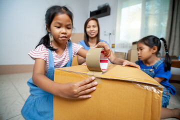 Asian child girls and their parents helping to pack the stuffs and tape a box before moving to new house on moving day. Home renovation and relocation concept.