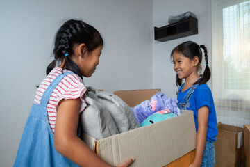 Two asian child girls carrying the big box with stuffs to help their parent moving to new house on moving day. Home renovation and relocation concept.