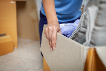 Close up on woman hand holding and carrying a cardboard box with stuffs moving to new house on moving day. Home renovation and relocation concept.