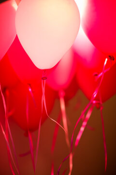 Pink flying balloons attached to string