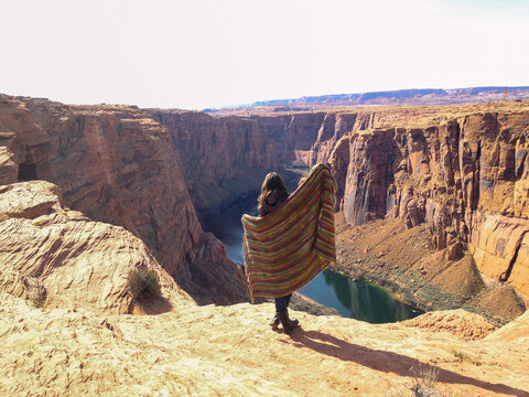 girl standing above canyon holding blanket