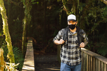 Man wearing face mask on a wooden bridge on the forest. New tourism during Covid-19 pandemic disease
