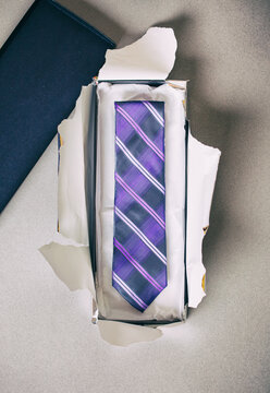 Ties: Purple Necktie In Gift Box With Wrapping Paper Ripped Open