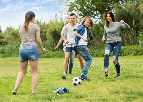 Group of happy teenagers playing football together on green lawn in park .