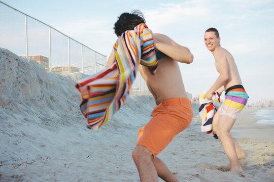 Young Men Friends Playing Snap Towel at each other on Sunny Summer Day in Rockaway Beach