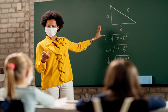 Black teacher wearing face mask while explaining math lesson in the classroom.