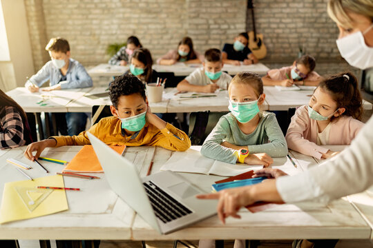 Elementary students wearing face masks while using laptop with their teacher in the classroom.
