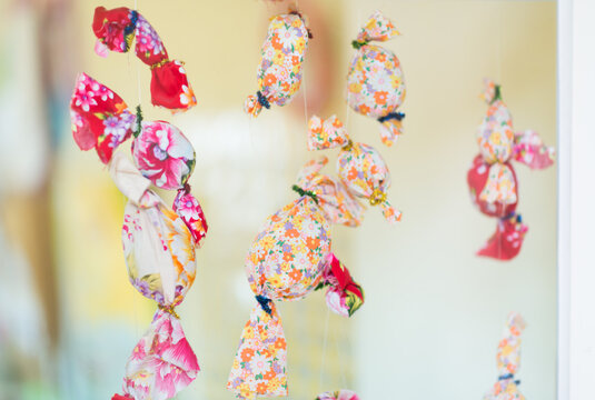 Candy shape ornament made by floral clothes hanging on window