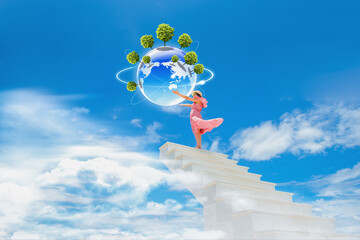 Beautiful woman holding a globe on a staircase, environmental concept.